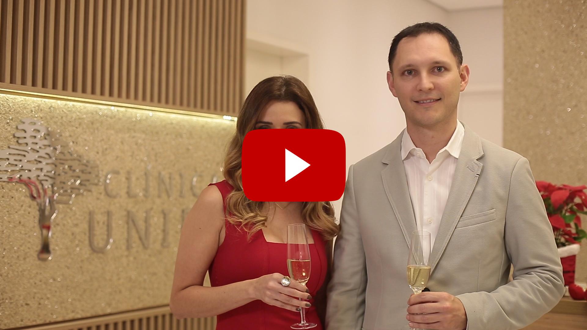 Dra. Paola e Dr. André, em frente ao logotipo de clínica Unire, desejam boas festas.